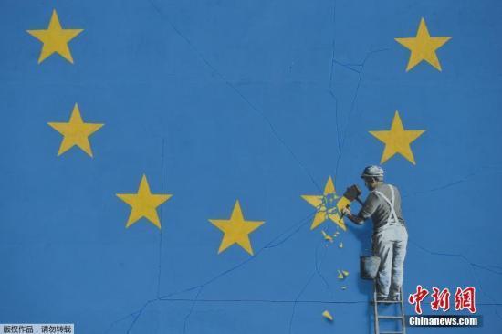 原料图:2017年5月7日,英国多佛,别名街头艺术家班克西创作了一幅画,画面中别名工人正从欧盟12星旗帜上抹失踪一颗星,寓意着英国将脱离欧盟。