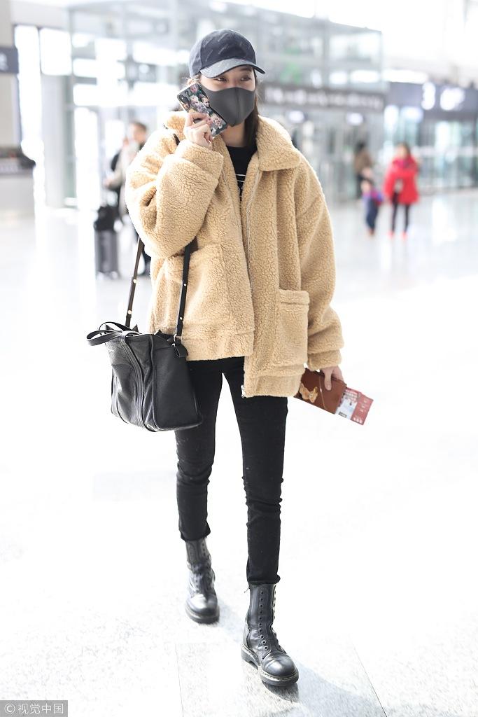 欧阳娜娜搭配修身黑色牛仔裤和马丁靴,视觉上营造出秀场又笔直的腿部图片