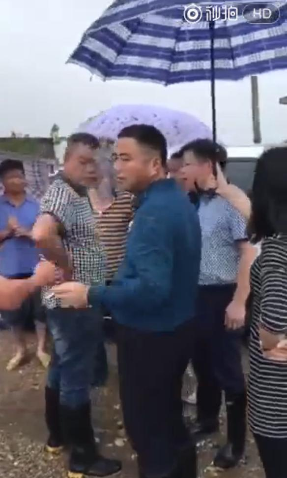 湖南一官员受灾民众前抽烟嚼槟榔_还有女子帮撑伞