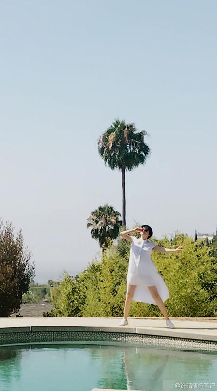 照片中她身穿白色连衣裙在泳池边跳跃奔跑,长腿肤白,身姿曼妙仍如少女