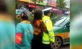 女司机违停被查狂追警车 背后拦腰拥抱民警不放手