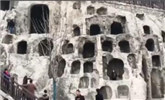 为与佛身合影留念 游客攀爬龙门石窟佛洞