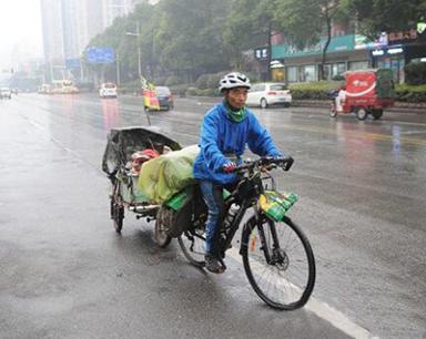 """男子辞职后拖着""""行李""""骑到长沙 宣传低碳出行"""