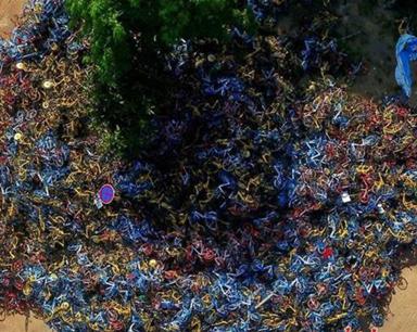 """海口惊现共享单车""""坟墓"""" 万辆共享单车堆积如山 城管要求25日前清理完毕"""