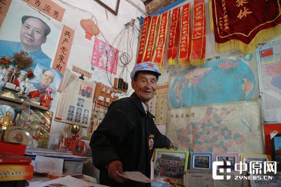 简陋的房间里摆满了老人的荣誉和自学报刊
