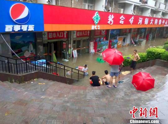 """图为河南师范大学校园内商铺被淹,学生,商家被""""困""""在台阶上."""