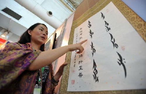 资料图片:2013年9月7日,在第四届中国桂林国际旅游博览会上,一名来自湖南省江永县的女子在推介一幅女书艺术作品。新华社记者陆波岸摄