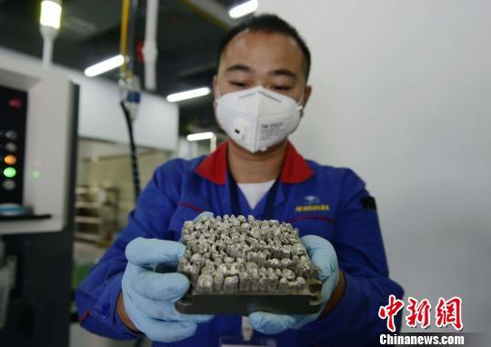华曙高科的工作人员展示刚刚用3D打印出来的义齿金属基底。 杨华峰 摄