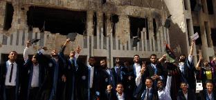 利比亚大学遭战火摧毁 学生在炮弹废墟前拍毕业照