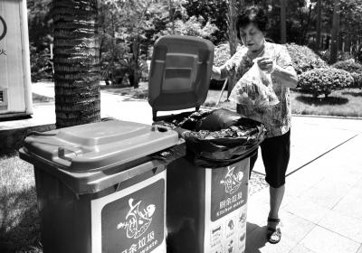 小区居民将厨余垃圾倒入专用垃圾桶里