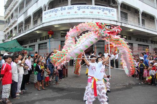 资料图:在柬埔寨首都金边,柬埔寨华侨华人社团的醒狮团在柬华理事总会门前表演舞龙。