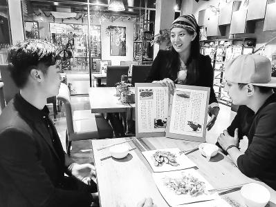 石晏菱(中)在向顾客介绍餐厅的菜品。