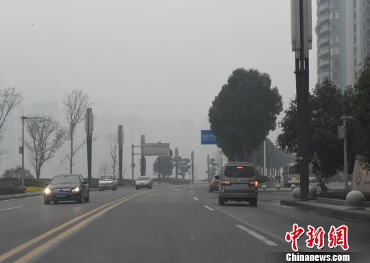 """图为重庆遇""""霾""""伏,能见度低,行驶在路上的车辆在白天也打开了车灯。周毅 摄"""
