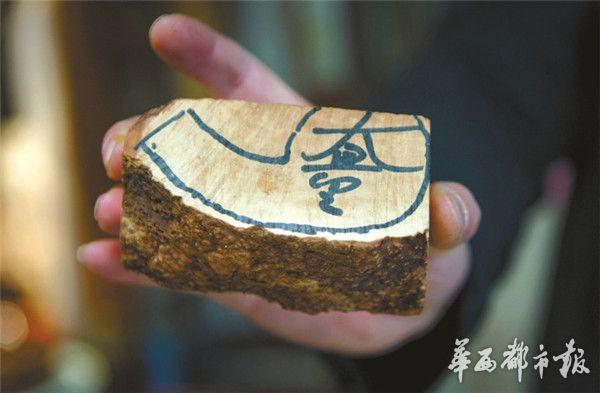 马勇手中的这块石楠树根,大师已经画好了斗形.