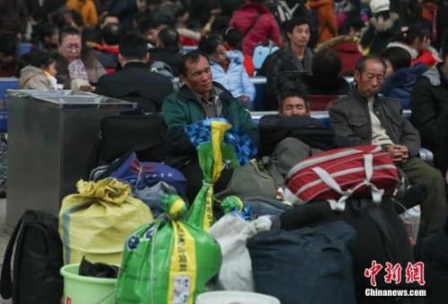 1月16日,武汉汉口火车站候车大厅里,等待进站上车的乘客进入了梦乡。中新社记者 张畅 摄
