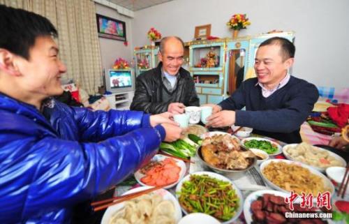 资料图:辽宁省葫芦岛市民在家中与家人享受丰盛的年夜饭。中新社发于海洋摄