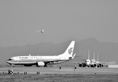 飞机在北京首都机场中跑道上等候起飞(3月31日摄)