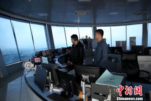 """图为塔台管制室内,管制员正在""""指挥""""飞机。"""