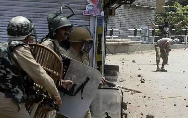 △印控克什米尔地区,戴着面具的抗议者朝当地的警察抛掷石块图自视觉中国