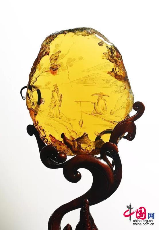 《文王拜相》 设计、制作:彭赣闽 琥珀质地通透,色彩鲜亮,莹莹生光,天然品相绝佳。作者最大限度的保留了琥珀的原始形制,只以阴雕技法刻画出周文王和姜子牙江边对话的情境,主旨鲜明。更有远山灵秀、嘉树葳蕤、静水流深的细节描摹,唯美的景致侧面烘托了人物的贤德与智慧,极富艺术感染力,令人回味悠长。