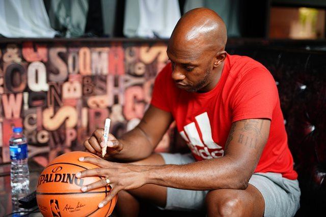 昌西•比卢普斯在篮球上签名,图片来源于天梭。