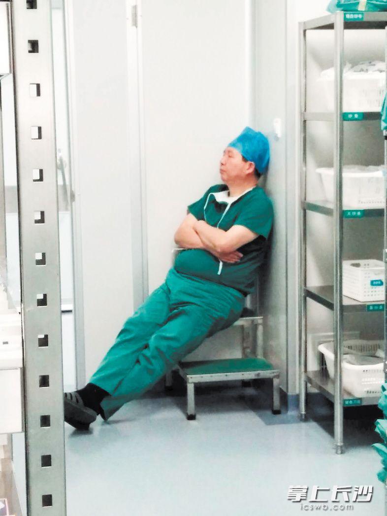 """市四医院医生贺健军连续手术8个小时后,在手术室一角打盹,被网友称为""""最美睡姿""""。  长沙晚报通讯员赵倩摄"""