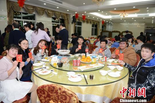 """参加年夜饭的华侨大学境外生们展示学校派发的""""压岁钱""""。 张为健摄"""