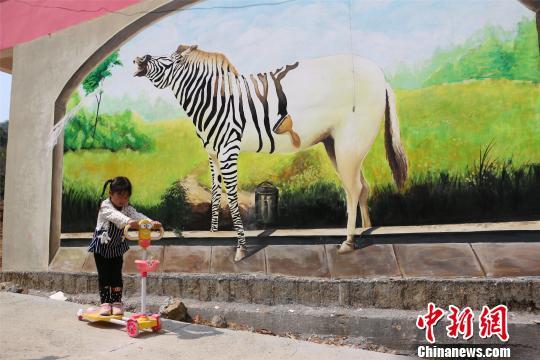 图为一小朋友在改造后的3D涂鸦墙前玩耍。 王以照摄