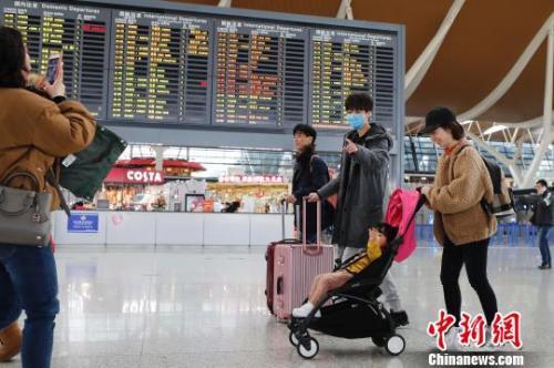 旅客带着孩子前往办票柜台办理登机手续。 殷立勤摄