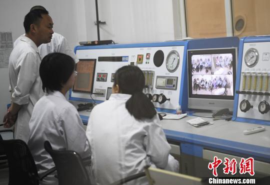 5月15日下午,成都市第一人民医院医生通过监控观察高压氧仓内治疗情况。 安源摄