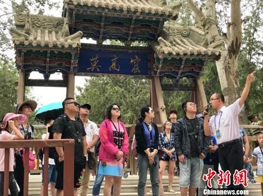 图为在敦煌莫高窟窟区外,莫高窟讲解员边磊(右一)向游客讲解。 闫姣摄
