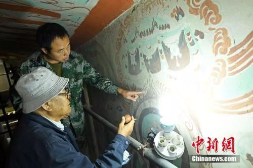 图为李云鹤在莫高窟姊妹窟榆林窟中修复壁画。(杨艳敏摄)