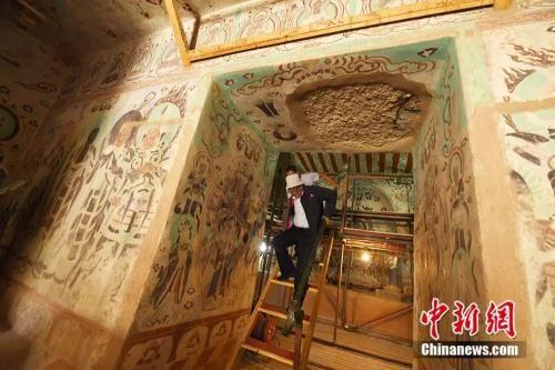 李云鹤的腿在一次赴外地修复文物时受了轻伤,上下梯子时极不便利。(杨艳敏摄)