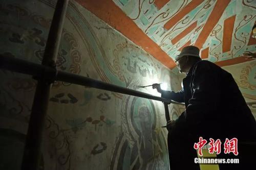 年逾八旬的李云鹤身体还算硬朗,洞窟里一坐下来就是数个小时。(杨艳敏摄)