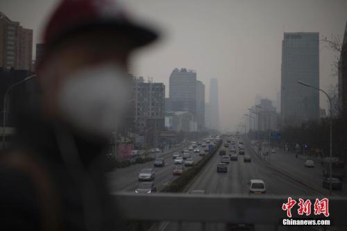 资料图:北京市民在雾霾中出行。中新社记者刘关关摄