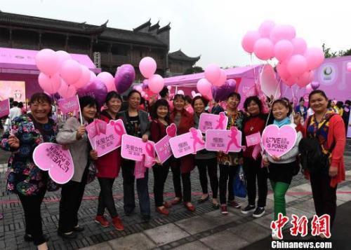 """资料图:重庆市民手举""""关爱女性健康""""等字样牌子,呼吁大家关爱女性。 周毅摄"""