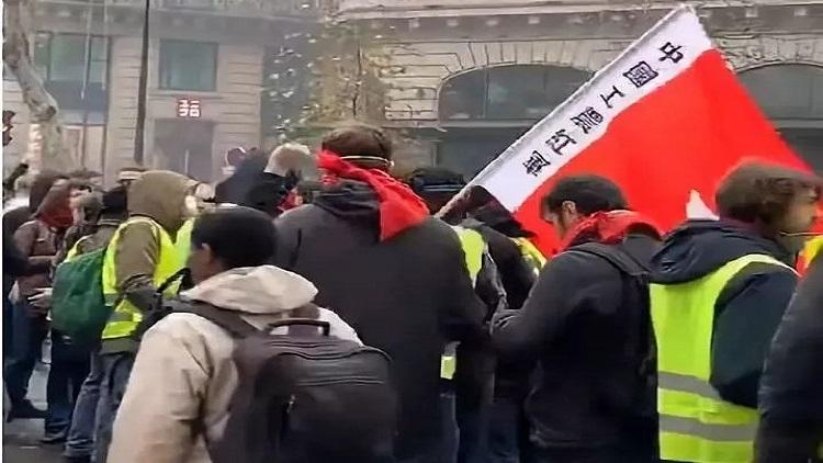 """▲在聚集于奥斯曼大街的一群示威者中,有人打出""""中国工农红军""""旗帜。图/欧洲时报微博视频截图"""