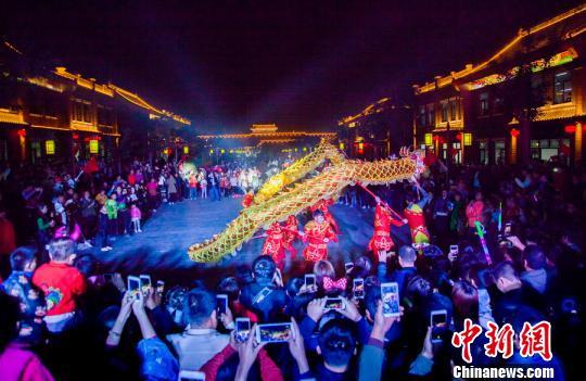 游客在围观舞龙表演。 武志伟摄