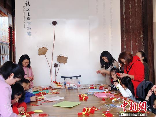 家长带着小朋友参与趣味手工体验活动。 叶秋云摄