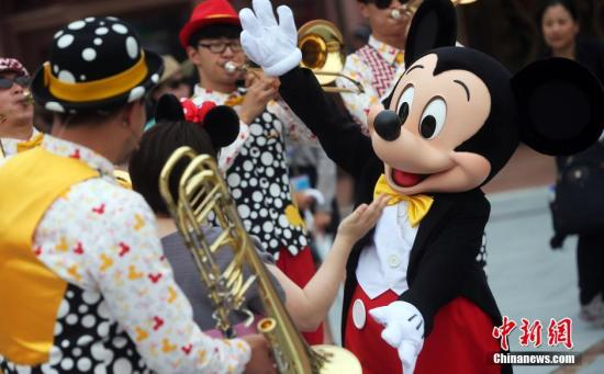 """资料图:6月15日,上海迪士尼乐园举行""""米奇童话专列""""主题巡游。上海迪士尼开幕在即,从14日开始为期3天的上海迪士尼乐园开幕庆典系列活动吸引了近千名嘉宾前来感受迪士尼的无穷魅力。 汤彦俊摄视频:上海迪士尼抢先看:光影迪士尼夜游也精彩来源:中国新闻网"""