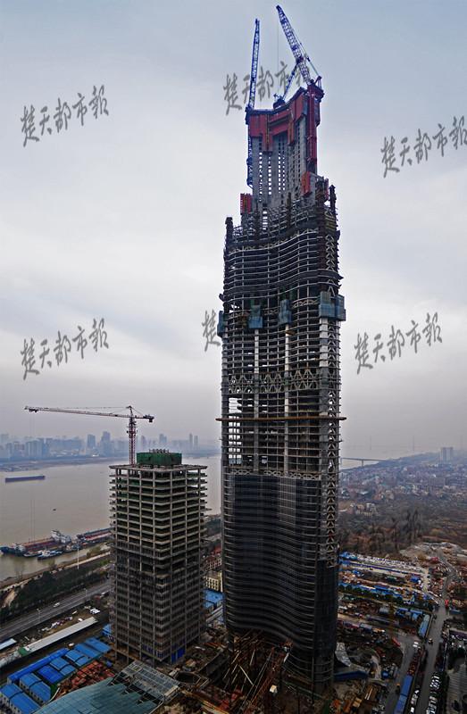 """1909年,41.3米高的汉口水塔建成,长时间成为武汉第一高楼。1984年,88.6米的晴川饭店建成。上世纪90年代起,武汉掀起超高层建筑建设""""热潮"""",1996年176米的泰合广场、2010年333米高的民生银行大厦,先后刷新武汉天际线。 2015年4月,武汉中心大厦封顶,438米的高度成为武汉最高楼。今日,武汉绿地中心到达439米,成为武汉最新的城市天际线,未来还将继续""""长高""""。 据介绍,武汉绿地中心计划2017年主体结构封顶,达到636米,成为世界第三"""