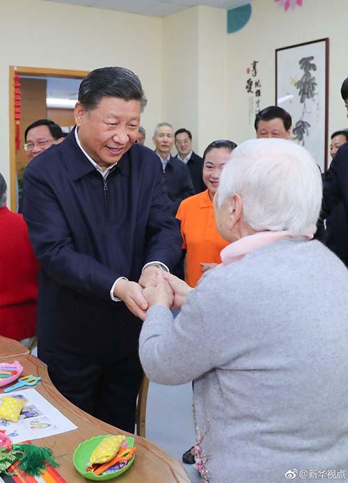 這是習近平在虹口區市民驛站嘉興路街道第一分站托老所同老年居民親切握手。 新華社記者謝環馳攝